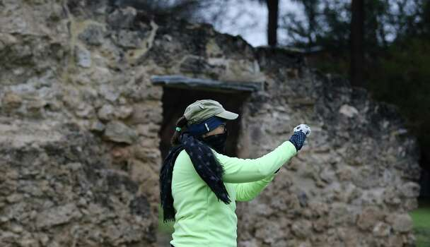 Kathy Hitt takes a selfie by Mission Concepcion before the start of the Missions Marathon Half run starting at Mission Concepcion on Saturday, Feb. 28, 2015. Despite near freezing temperatures and early drizzle, hundreds of runners were not dissuaded from taking part in the inaugural running event from which all proceeds went to the Las Misiones Permanent Fund which helps restore the four Spanish missions located in San Antonio: Mission Espada, Missoin San Jose, Mission San Juan and Mission Concepcion. Photo: Kin Man Hui, San Antonio Express-News / ©2015 San Antonio Express-News