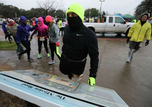 Buck Mejorado is shielded for the cold weather as he prepares to run in the Missions Marathon Half run starting at Mission Concepcion on Saturday, Feb. 28, 2015. Despite near freezing temperatures and early drizzle, hundreds of runners were not dissuaded from taking part in the inaugural running event from which all proceeds went to the Las Misiones Permanent Fund which helps restore the four Spanish missions located in San Antonio: Mission Espada, Missoin San Jose, Mission San Juan and Mission Concepcion. Photo: Kin Man Hui, San Antonio Express-News / ©2015 San Antonio Express-News