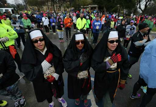 Mission Concepcion parishioners Melinda Barrera (from left), Candi Beltran and Mary Moncivais join in singing the National Anthem before running the Missions Marathon Half run starting at Mission Concepcion on Saturday, Feb. 28, 2015. Despite near freezing temperatures and early drizzle, hundreds of runners were not dissuaded from taking part in the inaugural running event from which all proceeds went to the Las Misiones Permanent Fund which helps restore the four Spanish missions located in San Antonio: Mission Espada, Missoin San Jose, Mission San Juan and Mission Concepcion. Photo: Kin Man Hui, San Antonio Express-News / ©2015 San Antonio Express-News