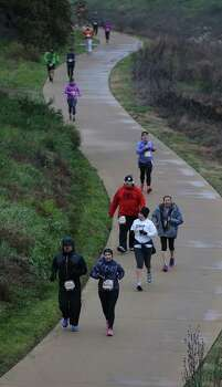 Runners make their way along a curved path along the Mission Reach while participating in the Missions Marathon Half run starting at Mission Concepcion on Saturday, Feb. 28, 2015. Despite near freezing temperatures and early drizzle, hundreds of runners were not dissuaded from taking part in the inaugural running event from which all proceeds went to the Las Misiones Permanent Fund which helps restore the four Spanish missions located in San Antonio: Mission Espada, Missoin San Jose, Mission San Juan and Mission Concepcion. (Kin Man Hui/San Antonio Express-News) Photo: Kin Man Hui, By Kin Man Hui/San Antonio Express-News / ©2015 San Antonio Express-News