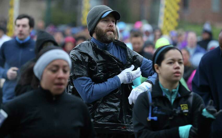 Runners used various methods to stay warm and dry as they leave the starting line of the Missions Marathon Half run starting at Mission Concepcion on Saturday, Feb. 28, 2015. Despite near freezing temperatures and early drizzle, hundreds of runners were not dissuaded from taking part in the inaugural running event from which all proceeds went to the Las Misiones Permanent Fund which helps restore the four Spanish missions located in San Antonio: Mission Espada, Missoin San Jose, Mission San Juan and Mission Concepcion. (Kin Man Hui/San Antonio Express-News)