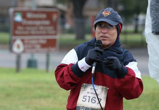 Father David Garcia addresses runners before the Missions Marathon Half run starting at Mission Concepcion on Saturday, Feb. 28, 2015. Despite near freezing temperatures and early drizzle, hundreds of runners were not dissuaded from taking part in the inaugural running event from which all proceeds went to the Las Misiones Permanent Fund which helps restore the four Spanish missions located in San Antonio: Mission Espada, Missoin San Jose, Mission San Juan and Mission Concepcion. Father Garcia also ran in the 5K portion of the event. (Kin Man Hui/San Antonio Express-News) Photo: Kin Man Hui, By Kin Man Hui/San Antonio Express-News / ©2015 San Antonio Express-News