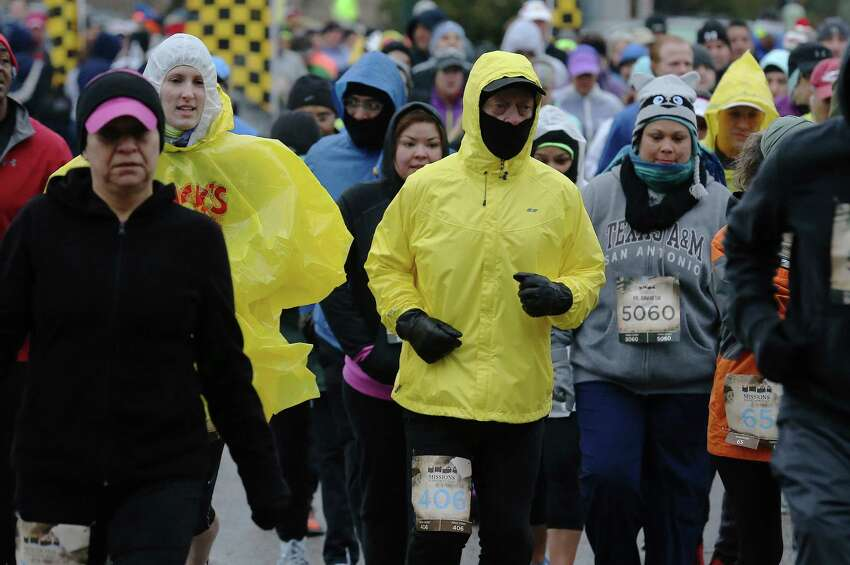Bundled up runners leave the starting line of the Missions Marathon Half run starting at Mission Concepcion on Saturday, Feb. 28, 2015. Despite near freezing temperatures and early drizzle, hundreds of runners were not dissuaded from taking part in the inaugural running event from which all proceeds went to the Las Misiones Permanent Fund which helps restore the four Spanish missions located in San Antonio: Mission Espada, Missoin San Jose, Mission San Juan and Mission Concepcion. (Kin Man Hui/San Antonio Express-News)