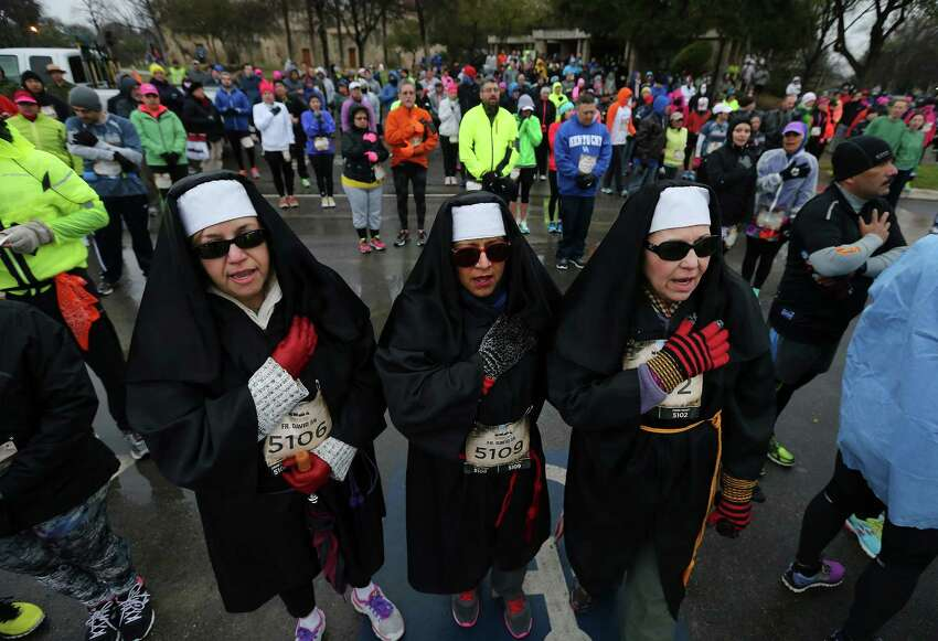 Mission Concepcion parishioners Melinda Barrera (from left), Candi Beltran and Mary Moncivais join in singing the National Anthem before running the Missions Marathon Half run starting at Mission Concepcion on Saturday, Feb. 28, 2015. Despite near freezing temperatures and early drizzle, hundreds of runners were not dissuaded from taking part in the inaugural running event from which all proceeds went to the Las Misiones Permanent Fund which helps restore the four Spanish missions located in San Antonio: Mission Espada, Missoin San Jose, Mission San Juan and Mission Concepcion. (Kin Man Hui/San Antonio Express-News)