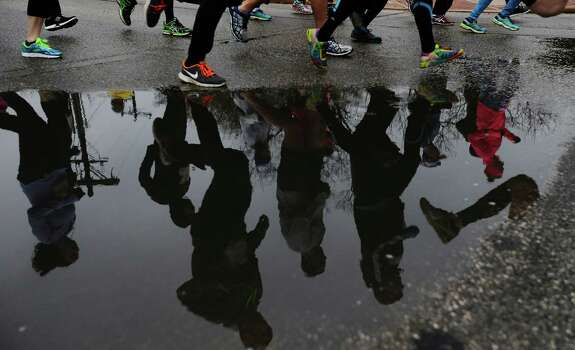 Runners stride past a pool of rain water at the start of the Missions Marathon Half run starting at Mission Concepcion on Saturday, Feb. 28, 2015. Despite near freezing temperatures and early drizzle, hundreds of runners were not dissuaded from taking part in the inaugural running event from which all proceeds went to the Las Misiones Permanent Fund which helps restore the four Spanish missions located in San Antonio: Mission Espada, Missoin San Jose, Mission San Juan and Mission Concepcion. (Kin Man Hui/San Antonio Express-News) Photo: Kin Man Hui, By Kin Man Hui/San Antonio Express-News / ©2015 San Antonio Express-News