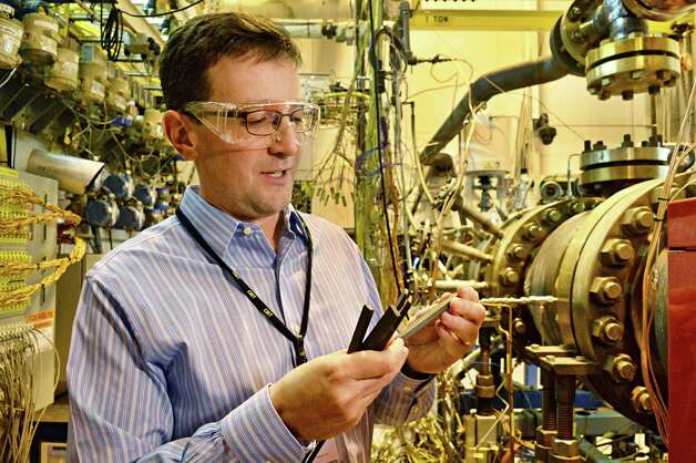 Jim Vartuli, manager of Ge Global Research's engineered ceramics lab, inspects silicon carbide ceramic matrix composite (CMC) test pieces in a combustion test cell Friday Feb. 27, 2015, in Niskayuna, NY.  (John Carl D'Annibale / Times Union) Photo: John Carl D'Annibale / 00030810A