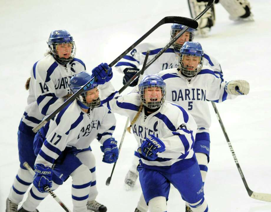 Darien's Sammy Nielsen, second from right, celebrates her game-tying goal with teammates from left, Julia Arrix (#14), Chandler Kirby (#17), Marissa Baker (#6) and Katie Zaro (#5)l in the third period of the FCIAC girls high school hockey final between Darien High School and Ridgefield High School at Terry Connors Rink in Stamford, Conn., Saturday afternoon, Feb. 28, 2015. The goal tied the game at one. Darien was crowned FCIAC Champ with a 3-1 victory over Ridgefield. Photo: Bob Luckey / Greenwich Time