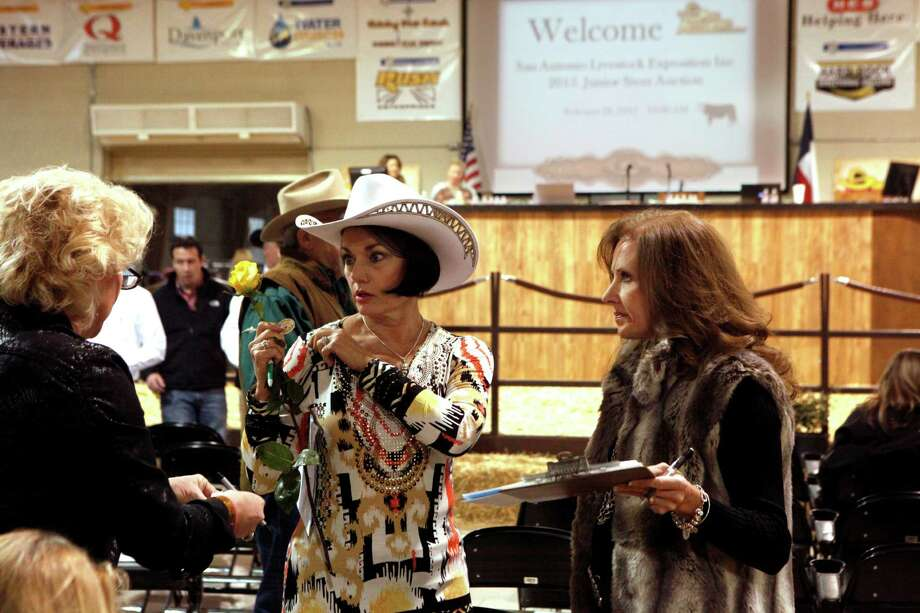 Traci Brodbeck (from left), Susan Parrish and Jill Metcalfe with the San Antonio Roses prepare for the San Antonio Stock Show & Rodeo Junior Steer Auction Saturday, Feb. 28, 2015. The San Antonio Roses, which has about 50 members which donate to the group, raise money over the year so that they can purchase steers in the livestock auction. Photo: Cynthia Esparza / For the San Antonio Express-News