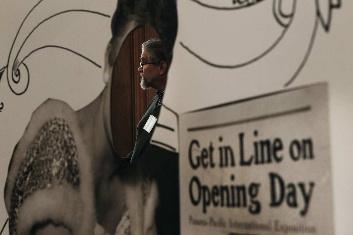 Jeff Thomas with the San Francisco Public Library seen through a face cutout, talks to visitors the SF History Expo in the Old Mint in San Francisco, Calif., Saturday February 28, 2015.