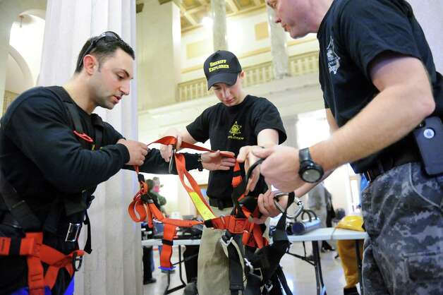 Sheriff explorer Jared Russom, 15, of Delmar, center, gets outfitted with a full-body harness used for search and rescue operations during the Albany County Sheriff's Open House on Saturday, Feb. 28, 2015, at the Albany County Courthouse in Albany, N.Y. Assisting him are deputies Tom Praisner, left, and Chad Hotaling. (Cindy Schultz / Times Union) Photo: Cindy Schultz / 00030802A