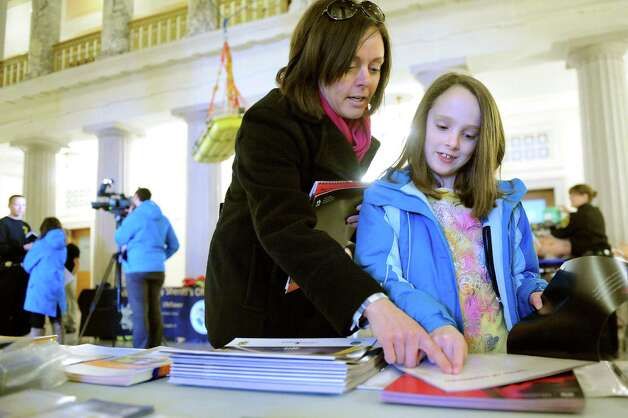 Sara Asher of Colonie, center, and her daughter Caitlyn Asher, 9, look over brochures and freebies at the information table during the Albany County Sheriff's Open House on Saturday, Feb. 28, 2015, at the Albany County Courthouse in Albany, N.Y. (Cindy Schultz / Times Union) Photo: Cindy Schultz / 00030802A