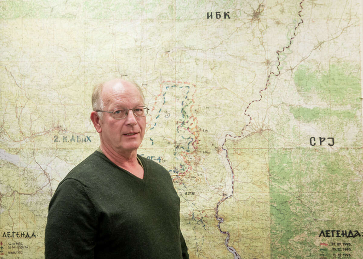 Michael MacQueen, of Immigration and Customs Enforce ment, stands in front of a tactical map of Bosnian Serb forces at Srebren ica.
