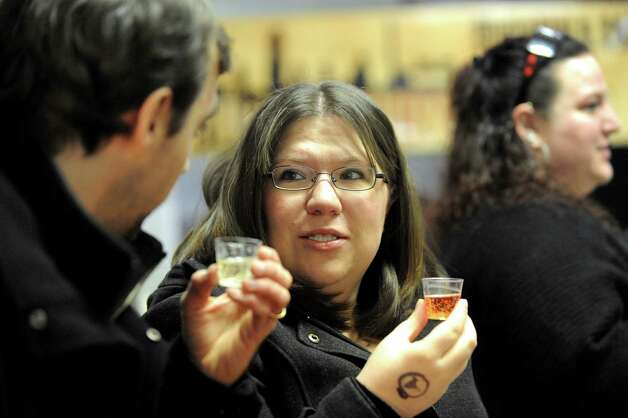 Jackie Bopp of Clifton Park, center, and her husband, Chris Bopp, try samples from state cideries during an one-year anniversary party on Saturday, Feb. 28, 2015, at Nine Pin Cider Works in Albany, N.Y. (Cindy Schultz / Times Union) Photo: Cindy Schultz / 00030817A