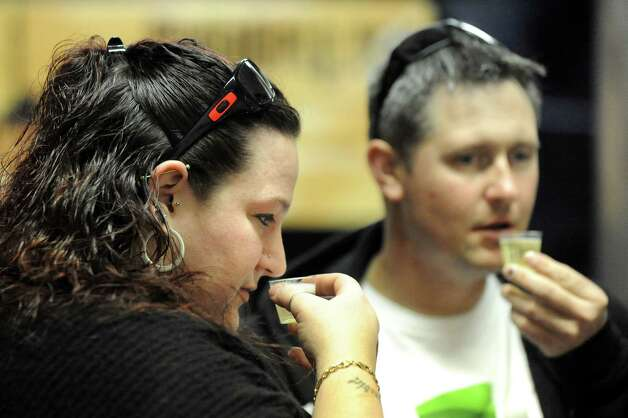 Jamelyn Dyer of Clifton Park, left, and her boyfriend, Chad Fritz, try hard cider samples from state cideries during an one-year anniversary party on Saturday, Feb. 28, 2015, at Nine Pin Cider Works in Albany, N.Y. (Cindy Schultz / Times Union) Photo: Cindy Schultz / 00030817A