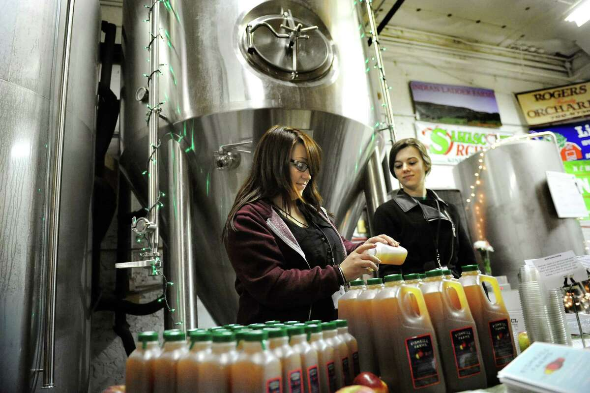 Fishkill Farms employees Kelly Clevenger, left, and Autumn Piazza serve samples of non-alcoholic cider during a one-year anniversary party on Saturday, Feb. 28, 2015, at Nine Pin Cider Works in Albany, N.Y. Located just over a half hour away from Danbury, Fishkill Farms is a 270-acre apple orchard and vegetable farm that has been around since the turn of the 20th centrury.
