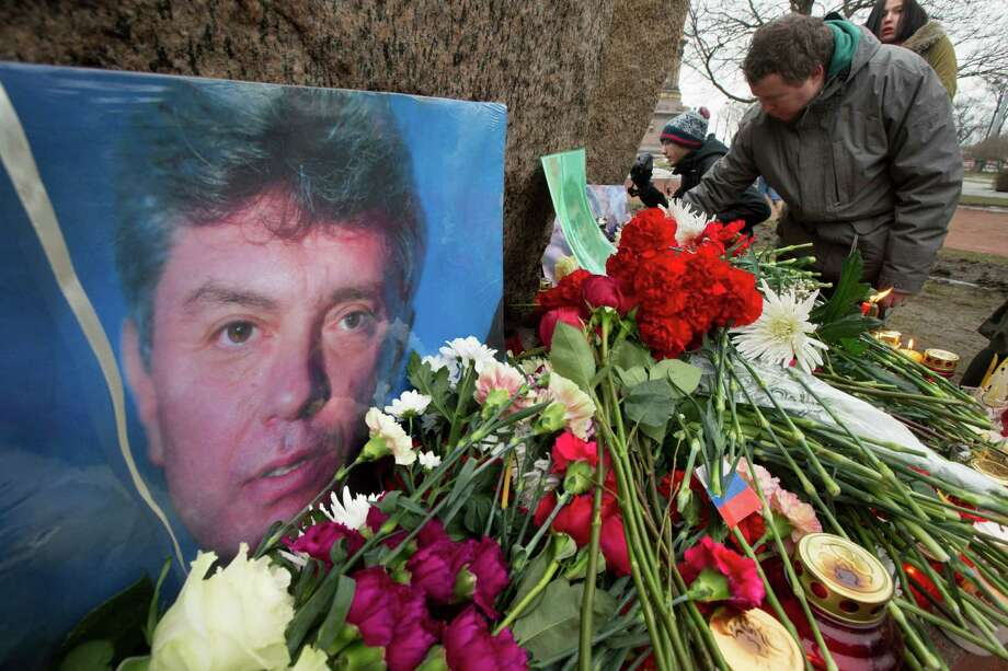 People lay flowers in memory of Boris Nemtsov at the monument of political prisoners Solovetsky Stone in central St. Petersburg, Russia, on Saturday. Nemtsov was gunned down near the Kremlin, just a day before a planned protest against the government. Photo: Dmitry Lovetsky /Associated Press / AP