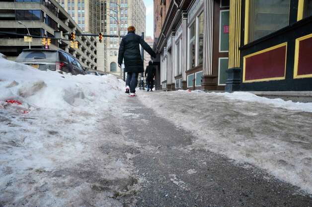 A woman navigates a narrow path worn through the ice covered sidewalk on South Pearl St. on Wednesday, Feb. 25, 2015, in Albany, N.Y.     (Paul Buckowski / Times Union)