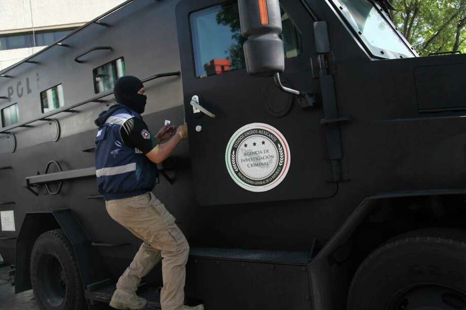 A masked federal police officer rides on the running board of an   armored vehicle in Mexico City. Photo: Marco Ugarte / Associated Press / AP