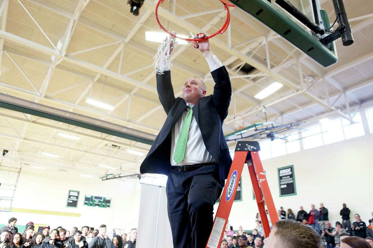 Sage men's basketball coach Brian Barnes cuts down the net after the top-seeded Gators won the Skyline Conference Tournament, and the automatic Division III NCAA Tournament bid that goes with it, by beating St. Joseph's (Long Island) 84-70 in the final on Saturday, Feb. 28. (Matt Milless / Sage College)