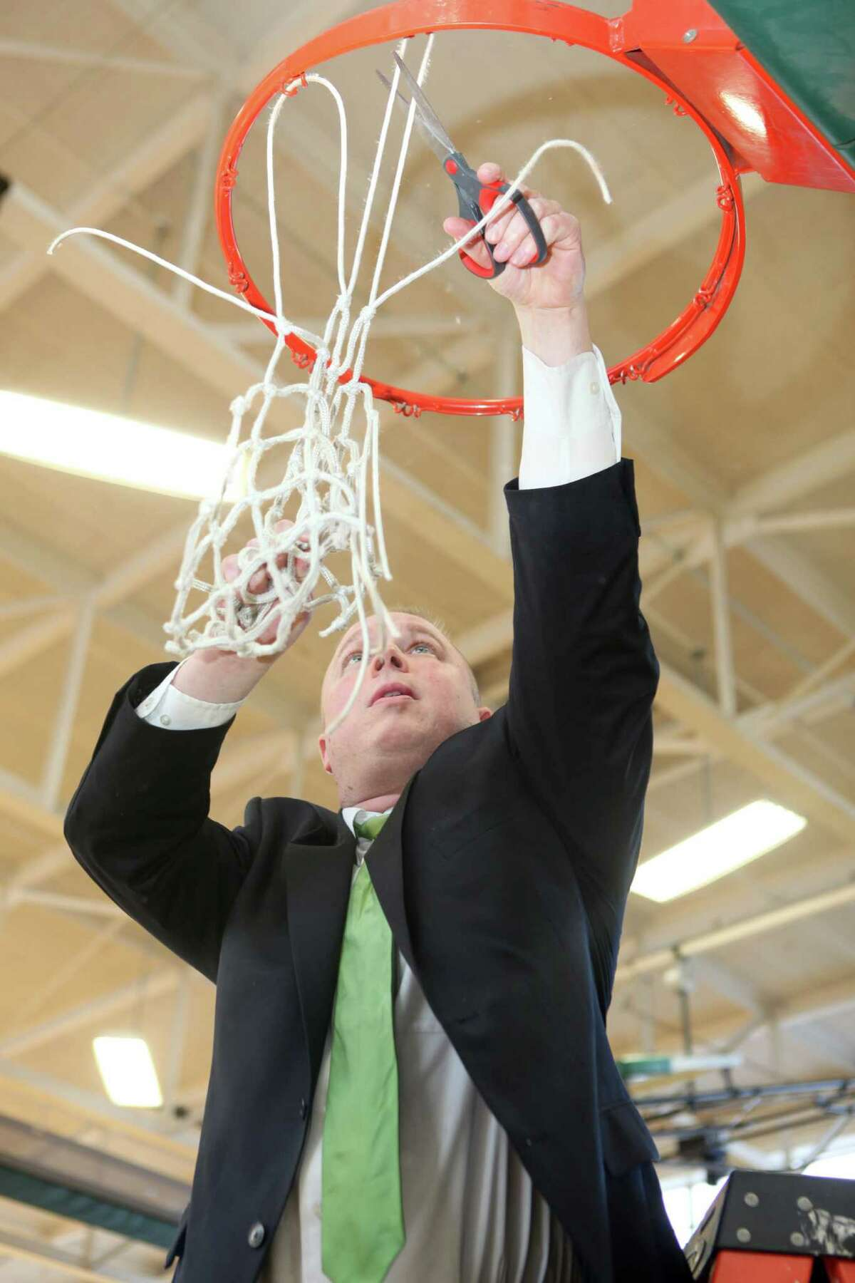 Sage men's basketball coach Brian Barnes cuts down the net after the Gators won the Skyline Conference Tournament, and the automatic Division III NCAA Tournament bid that goes with it, by beating St. Joseph's (Long Island) 84-70 in the final on Saturday, Feb. 28. (Matt Milless / Sage College)