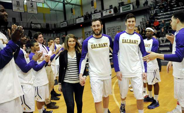 UAlbany Sam Rowley, center, is honored on senior day as he walks with his girlfriend Andrea Fazio, left, and brother Mike Rowley before their basketball game against Vermont on Saturday, Feb. 28, 2015, at UAlbany in Albany, N.Y. (Cindy Schultz / Times Union) Photo: Cindy Schultz / 00030743A