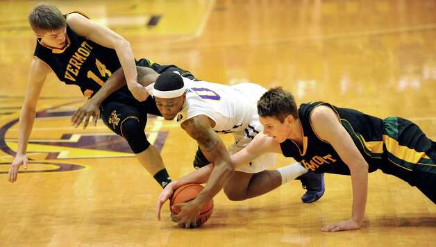 UAlbany'S Evan Singletary, center, battles for a loose ball against Vermont's Cam Ward, left, and Zach McRoberts defends during their basketball game on Saturday, Feb. 28, 2015, at UAlbany in Albany, N.Y. (Cindy Schultz / Times Union) Photo: Cindy Schultz / 00030743A