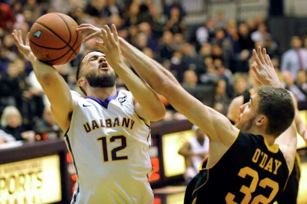 UAlbany'S Peter Hooley, left, draws a foul from Vermont's Ethan O'Day during their basketball game on Saturday, Feb. 28, 2015, at UAlbany in Albany, N.Y. (Cindy Schultz / Times Union) Photo: Cindy Schultz / 00030743A