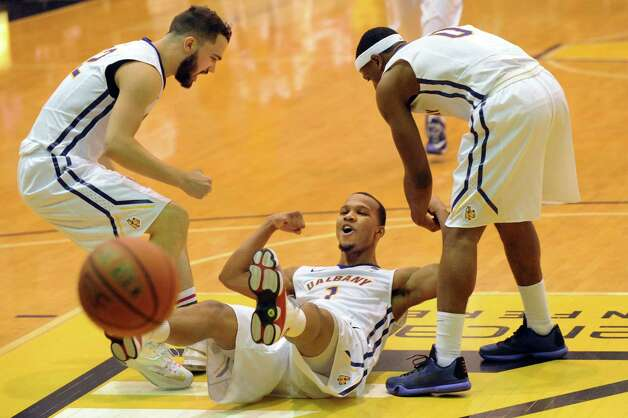 UAlbany's Ray Sanders, center, when he makes the basket and draws a foul during their basketball game against Vermont on Saturday, Feb. 28, 2015, at UAlbany in Albany, N.Y. Teammates Peter Hooley, left, and Evan Singletary help up Sanders. (Cindy Schultz / Times Union) Photo: Cindy Schultz / 00030743A