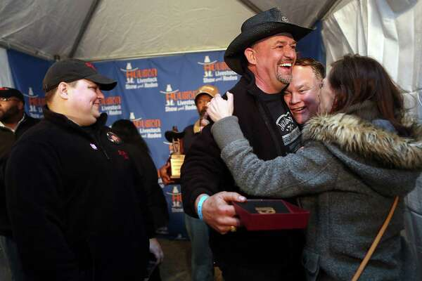 Teammates Doug Scheidling, David Spurlin, Holly Spurlin, and the rest of the 'Across the Track Cook-Off Team' celebrate winning the Grand Champion Overall in the 2015 Houston Livestock Show and Rodeo World's Champion Bar-B-Que Cookoff on Saturday, Feb. 28, 2015, in Houston.
