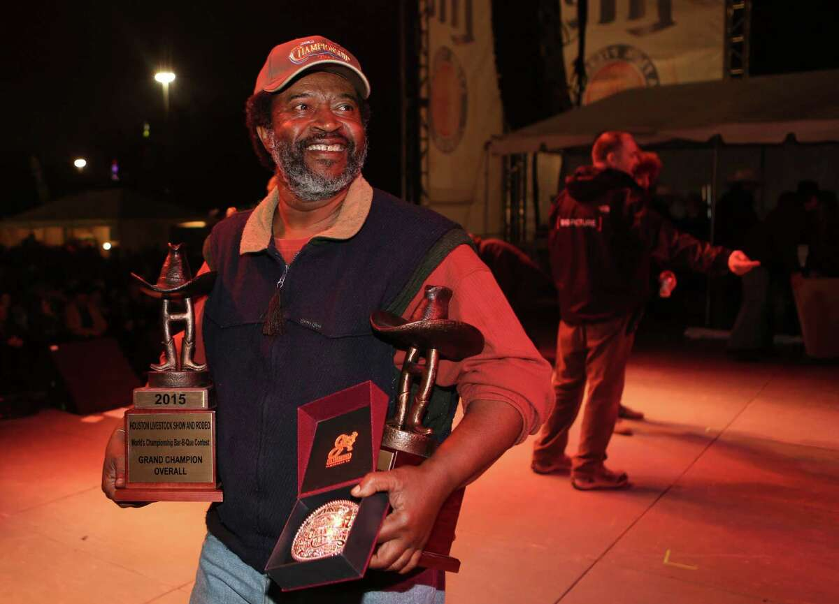 Kerry Fellows carries the trophies awarded to Across the Track Cook-Off Team for the 2015 Houston Livestock Show and Rodeo World's Champion Bar-B-Que Cookoff Grand Champion Overall winner on Saturday, Feb. 28, 2015, in Houston.