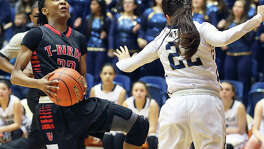 Wagner guard Kiana Williams angles around O'Connor's Amber Vidal for a layup during the Region IV-6A girls basketball final at the UTSA Convocation Center on Feb. 28, 2015.