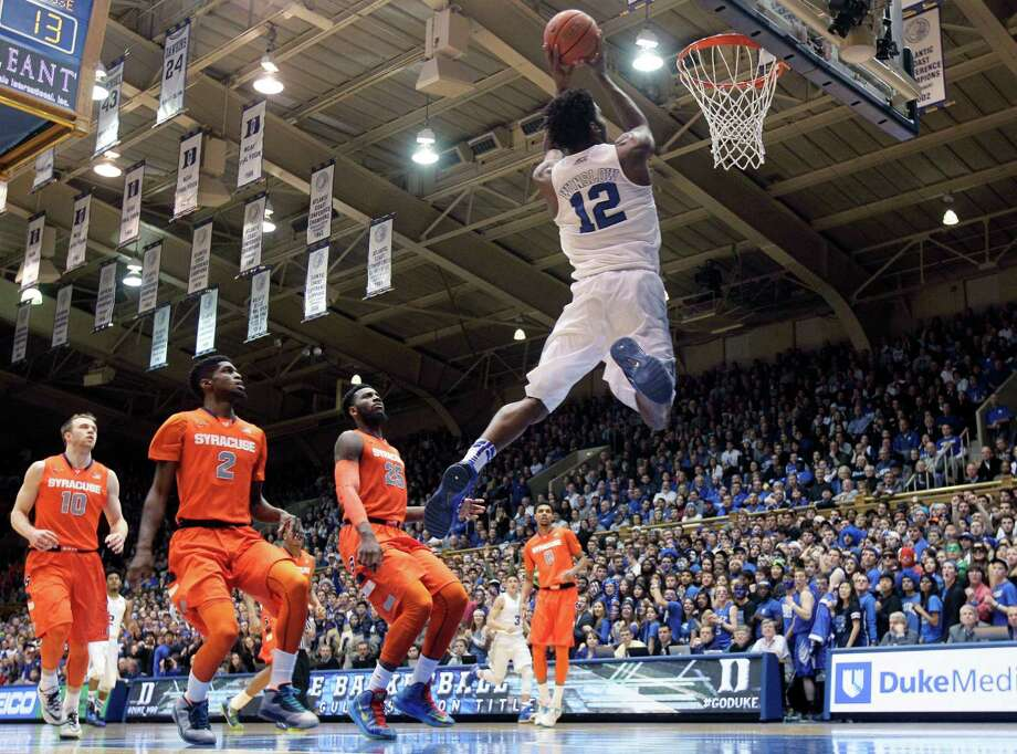 Duke's Justise Winslow (12) drives to the basket as Syracuse's Trevor Cooney (10), B.J. Johnson (2) and Rakeem Christmas (25) watch during the first half of an NCAA college basketball game in Durham, N.C., Saturday, Feb. 28, 2015. (AP Photo/Gerry Broome) ORG XMIT: NCGB105 Photo: Gerry Broome / AP
