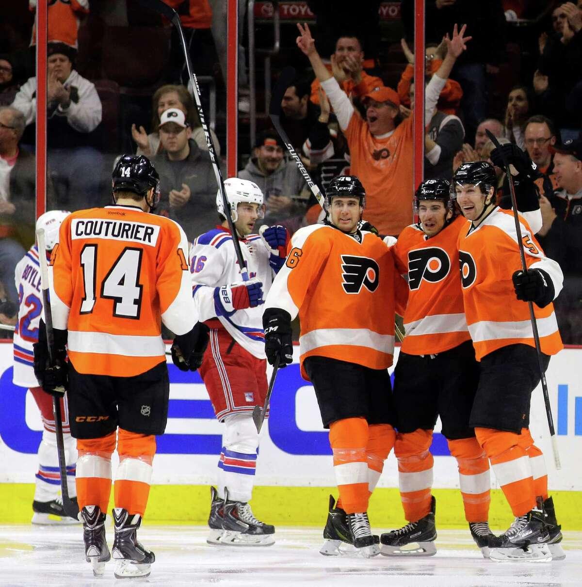 Philadelphia Flyers' Sean Couturier (14), Chris VandeVelde (76) Michael Del Zotto (15) and Braydon Coburn (5) celebrate after Del Zotto's go-ahead goal during the third period of an NHL hockey game against the New York Rangers, Saturday, Feb. 28, 2015, in Philadelphia. Philadelphia won 4-2. (AP Photo/Matt Slocum) ORG XMIT: PXC107