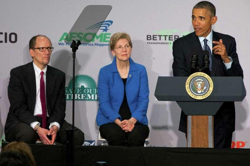 Labor Secretary Tom Perez and Sen. Elizabeth Warren, D-Mass., listen as President Barack Obama speak