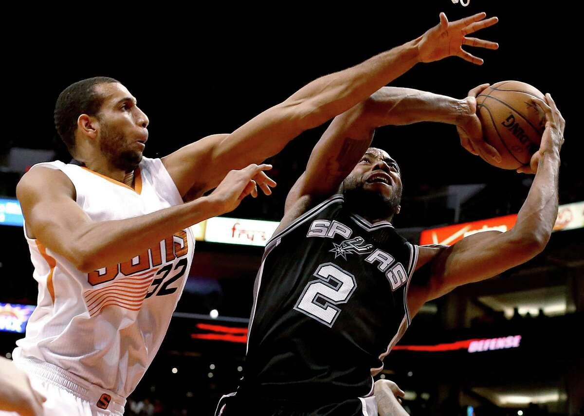 Phoenix Suns forward Brandan Wright (32) fouls San Antonio Spurs forward Kawhi Leonard during the third quarter of an NBA basketball game, Saturday, Feb. 28, 2015, in Phoenix. (AP Photo/Rick Scuteri)