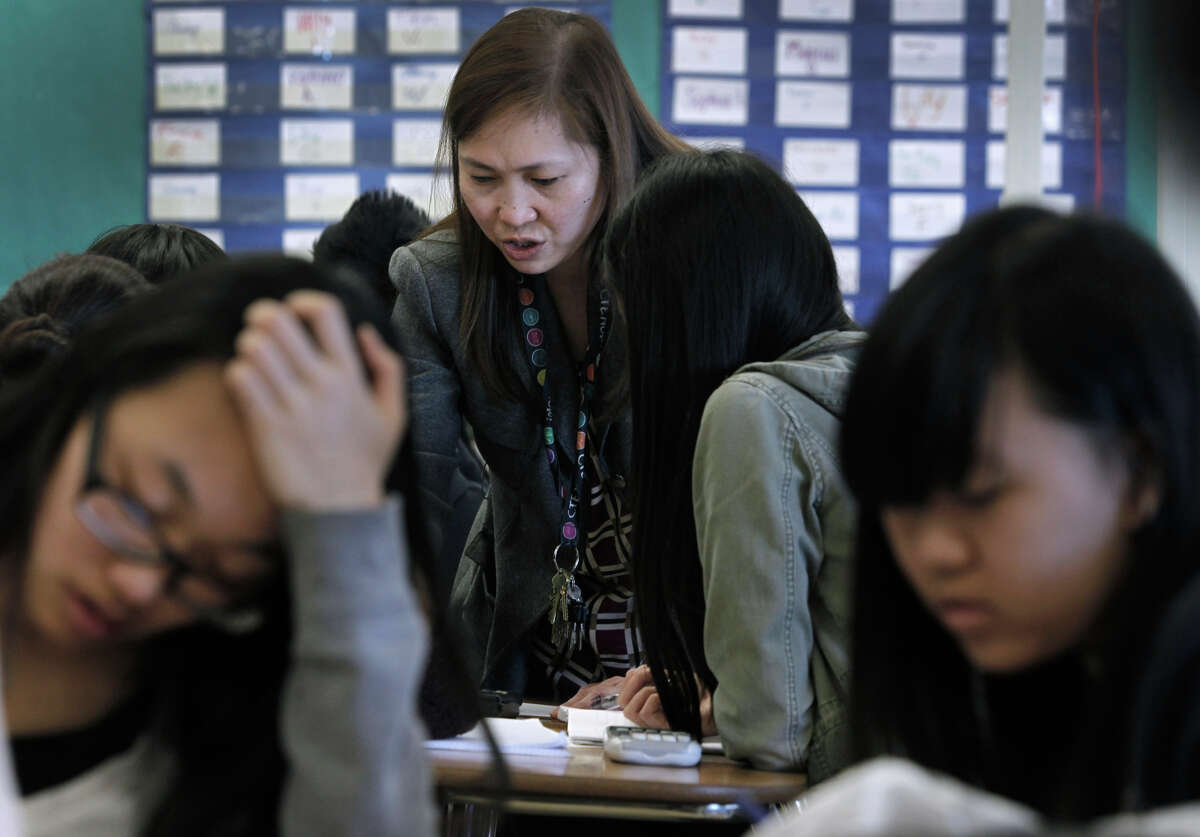 Teacher Mary Ann Castro helps students in Advanced Placement Calculus at Burton High School in S.F. Parents are not happy with the new sequence of math courses which delays Algebra 1 until ninth grade.