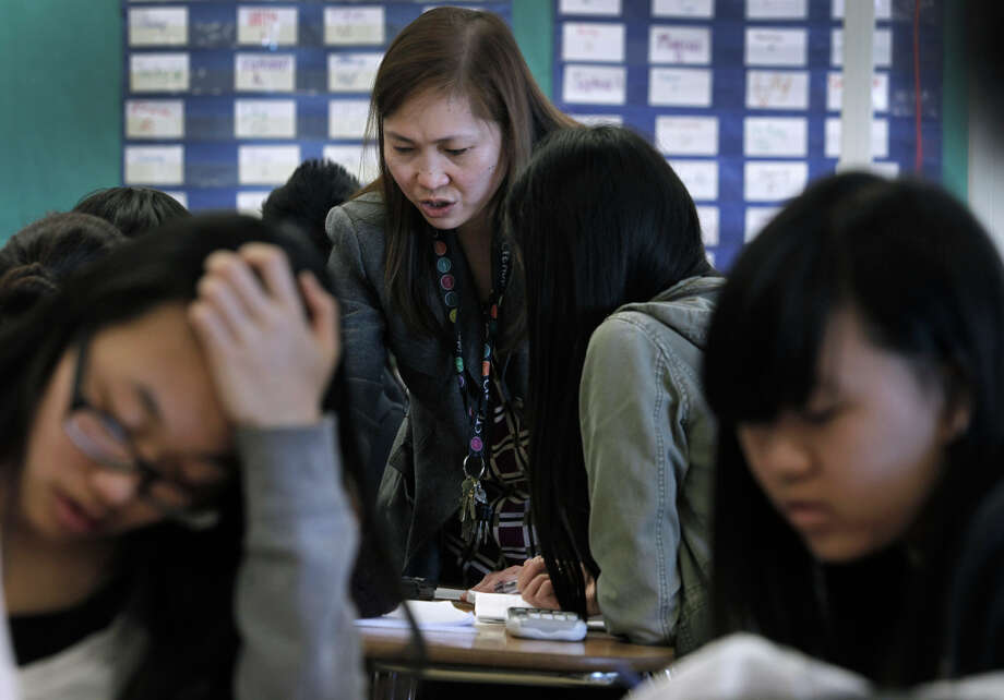 Teacher Mary Ann Castro helps students in Advanced Placement Calculus at Burton High School in S.F. Parents are not happy with the new sequence of math courses which delays Algebra 1 until ninth grade. Photo: Paul Chinn / The Chronicle / ONLINE_YES