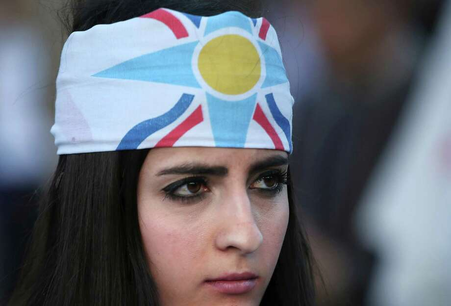 An Assyrian woman wears her community's flag as a headband during a protest in Beirut against the abduction of Assyrian Christians in Syria. Photo: Hussein Malla /Associated Press / AP
