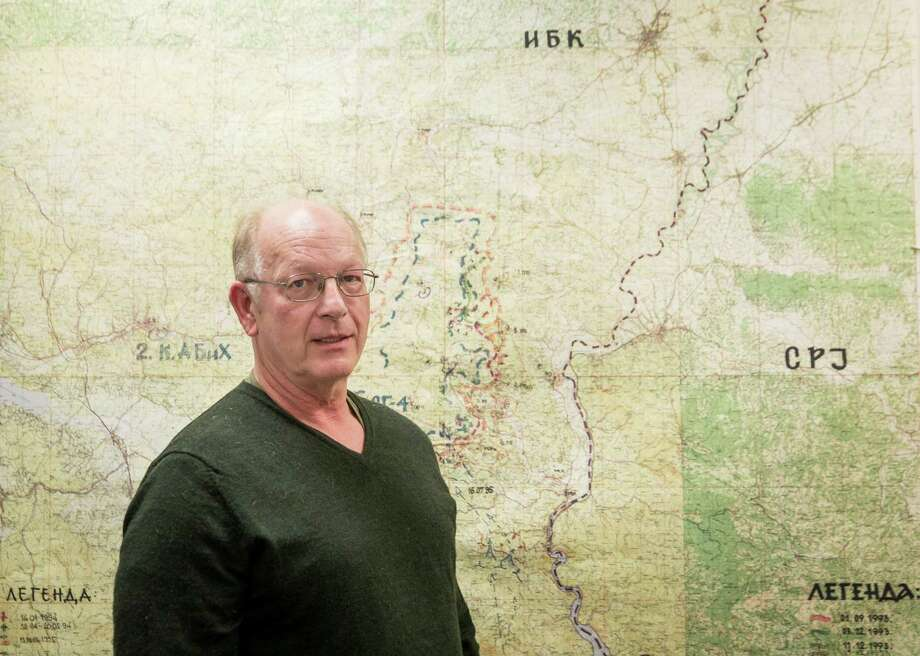 """The idea that the people who did all this damage in Bosnia should have a free pass and a new shot at life is just obscene to me,"" says ICE's Michael MacQueen, with a tactical map of Bosnian Serb forces at Srebrenica. with a tactical map of Bosnian Serb forces at Srebrenica, in Washington, Feb. 27, 2015. Immigration officials are moving to deport at least 150 Bosnians living in the U.S. who they believe took part in war crimes in the former Yugoslavia in the 1990s. âThe idea that the people who did all this damage in Bosnia should have a free pass and a new shot at life is just obscene to me,â said MacQueen. (Drew Angerer/The New York Times) Photo: Drew Angerer /New York Times / NYTNS"