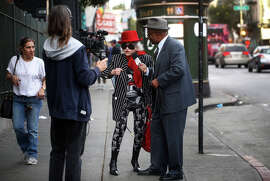 "Performing as the host of ""The Mister Geoffrey Show,"" Geoffrey Grier interviews Deborah Marinoff in San Francisco's Tenderloin neighborhood to get a better understanding of the residents in the area."
