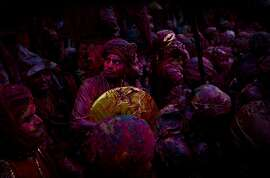 Indian Hindu devotees smeared with colors visit the Nandagram temple, famous for Lord Krishna and his brother Balram, during Lathmar holi festival, in Nandgaon, India, Saturday, Feb. 28, 2015. During Lathmar Holi the women of Nandgaon, the hometown of Krishna, beat the men from Barsana, the legendary hometown of Radha, consort of Hindu God Krishna, with wooden sticks in response to their teasing as they depart the town. (AP Photo/Saurabh Das)