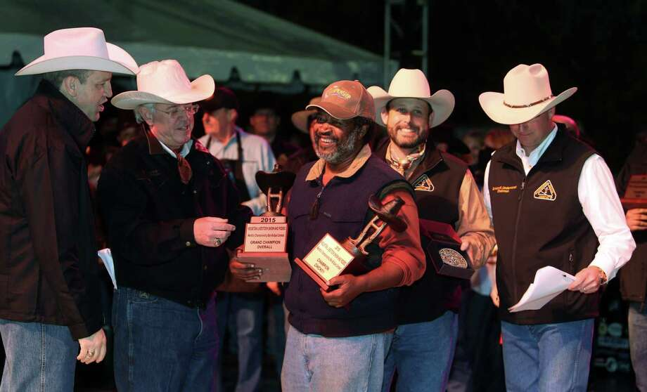 """Across the Track Cook-Off Team"" is awarded the Grand Champion Overall winner for the 2015 Houston Livestock Show and Rodeo World's Champion Bar-B-Que Cookoff and representative Kerry Fellows receives the award on Saturday, Feb. 28, 2015, in Houston. Photo: Mayra Beltran, Houston Chronicle / © 2015 Houston Chronicle"
