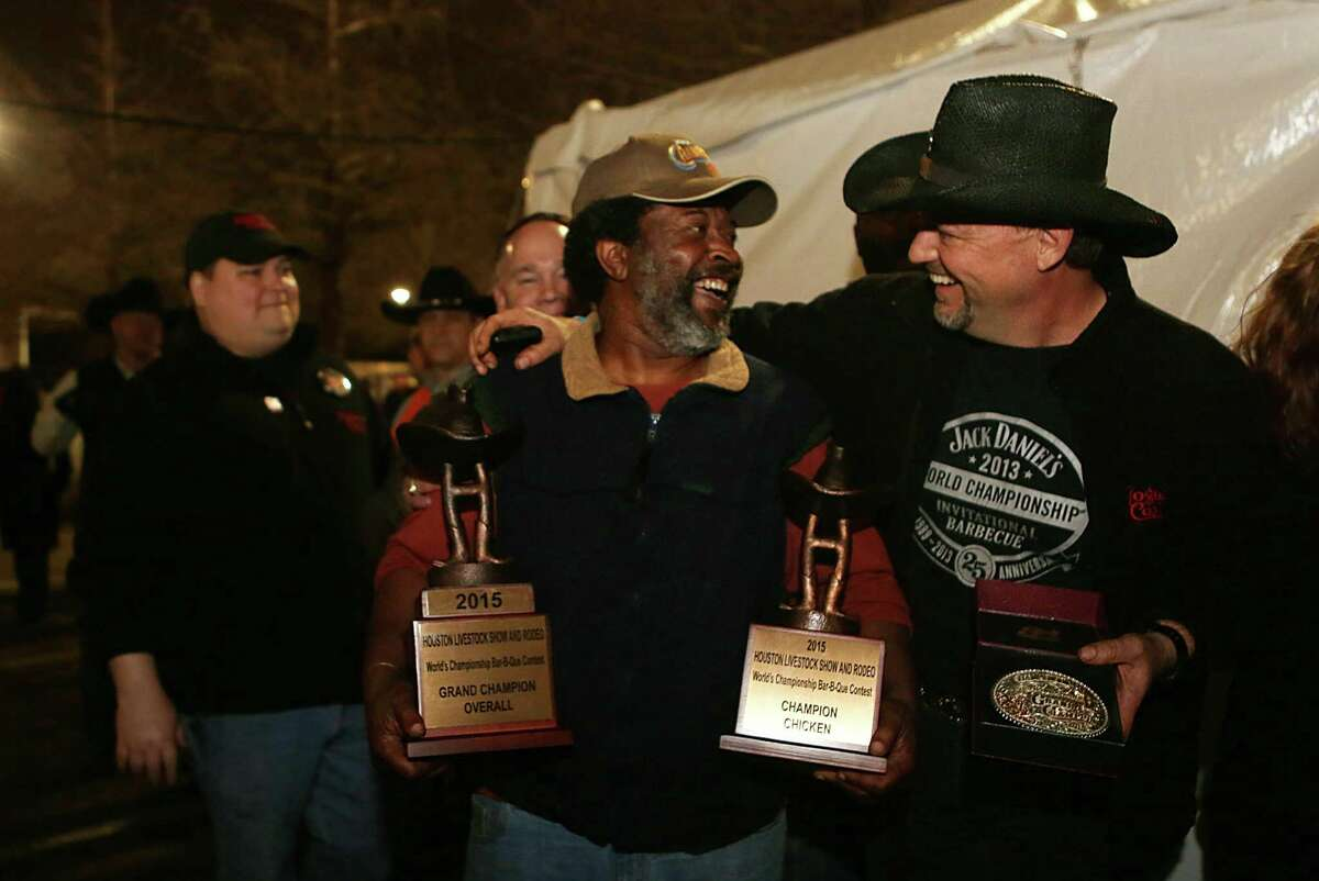 Teammates Kerry Fellows and Doug Scheidlng carry the trophy awarded to Across the Track Cook-Off Team for the 2015 Houston Livestock Show and Rodeo World's Champion Bar-B-Que Cookoff Grand Champion Overall on Saturday, Feb. 28, 2015, in Houston.
