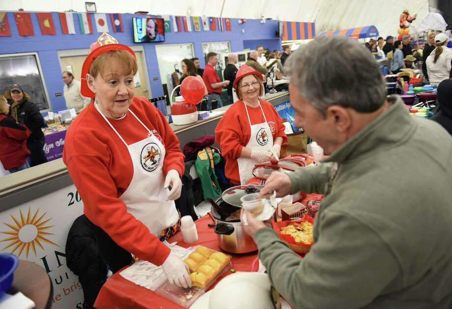 Ethel Sweet, left, and Ruth Cote, of the Miry Brook Ladies Auxilary, serve chili to Jimmy Lalos, of Danbury, during the seventh annual Chili Winter Warm-Up at the Danbury Sports Dome in Danbury, Conn. Sunday, March 1, 2015.  The event included chili sampling and a competition between dozens of local groups, restaurants and the general public.  Also at the festival were soccer games, face painting, coloring, a magician and live music from Dave King and the Mad Hatters. Photo: Tyler Sizemore / Greenwich Time