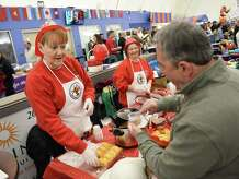 Ethel Sweet, left, and Ruth Cote, of the Miry Brook Ladies Auxilary, serve chili to Jimmy Lalos, of Danbury, during the seventh annual Chili Winter Warm-Up at the Danbury Sports Dome in Danbury, Conn. Sunday, March 1, 2015.  The event included chili sampling and a competition between dozens of local groups, restaurants and the general public.  Also at the festival were soccer games, face painting, coloring, a magician and live music from Dave King and the Mad Hatters.