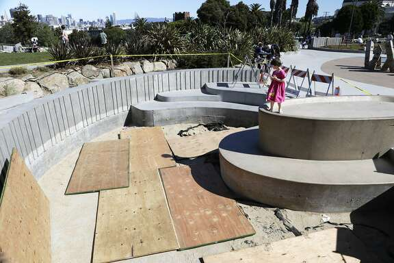 Jaqueline Finney (4) of San Francisco looks into the sandbox in the children's playground at Dolores Park in San Francisco on Sunday, March 1, 2015. The sandbox was found full of broken glass bottles on Friday, forcing maintenance staff to replace all of its sand.