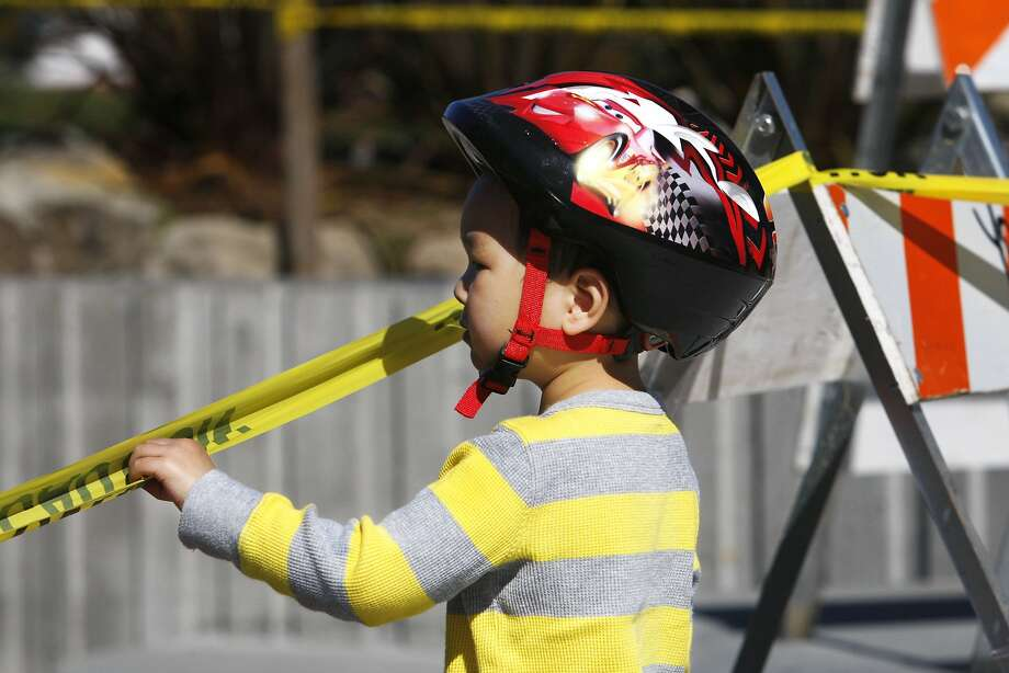 Zachary Jen (3), of San Francisco, peers across caution tape into the sandbox at Dolores Park in San Francisco on Sunday, March 1, 2015. The sandbox was found full of broken glass bottles on Friday, forcing maintenance staff to close it while they replace the sand. Photo: Terray Sylvester, The Chronicle