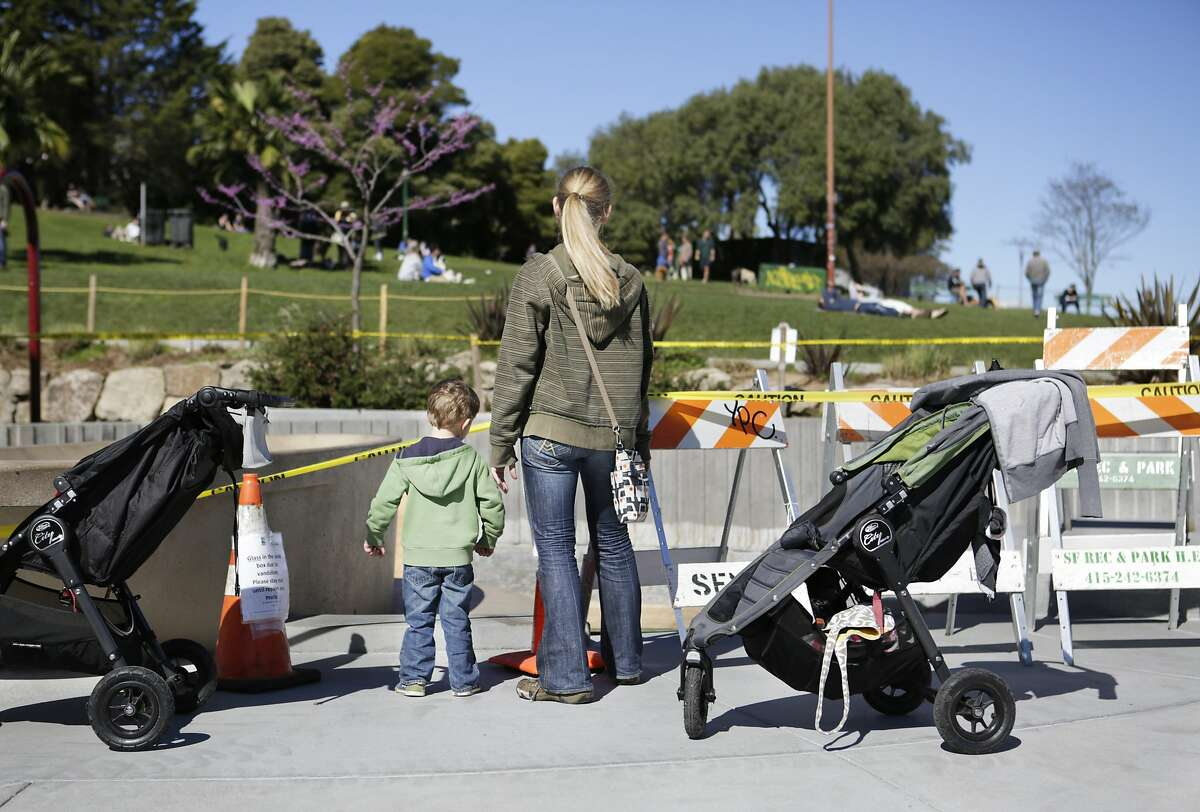 Theo Wolens (3) and his mother, Katie Lamont, look into the empty sandbox in the children's playground at Dolores Park in San Francisco on Sunday, March 1, 2015. The sandbox was found full of broken glass bottles on Friday, forcing maintenance staff to replace all of its sand.