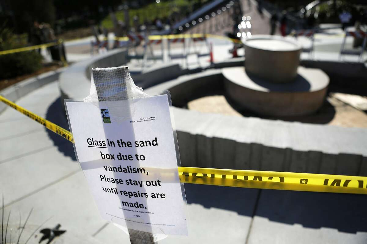 A warning sign is seen in the children's playground at Dolores Park in San Francisco on Sunday, March 1, 2015. The sandbox was found full of broken glass bottles on Friday, forcing maintenance staff to replace all of its sand.