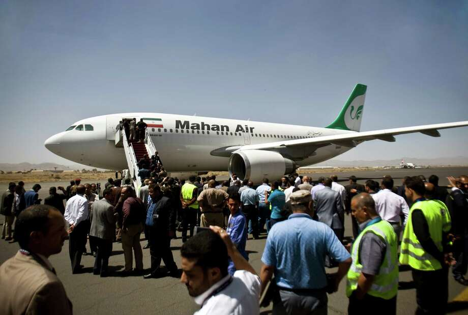 Yemeni airport, security and transportation officials greet a plane from the Iranian private airline, Mahan Air after it lands at the international airport in Sanaa, Yemen, Sunday, March 1, 2015. The first direct flight from Iran to the rebel-held Yemeni capital arrived, Sunday, an Airbus 310 carrying Iranians including aid workers from the Iranian Red Crescent as Yemen's Shiite rebels formalize ties with the regional Shiite powerhouse. The rebels, who overran the capital, Sanaa, last September, are widely believed to have support from Iran, a claim they frequently denied. (AP Photo/Hani Mohammed) Photo: Hani Mohammed / Associated Press / AP